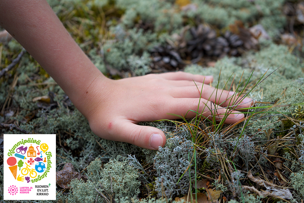 Lapsen käsi metsässä sammaleen päällä.