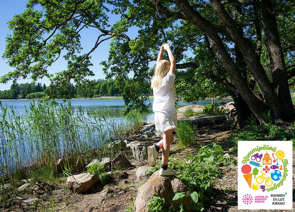Tyttö tasapainoilee yhdellä jalalla kiven päällä kesäisen järven rannalla.