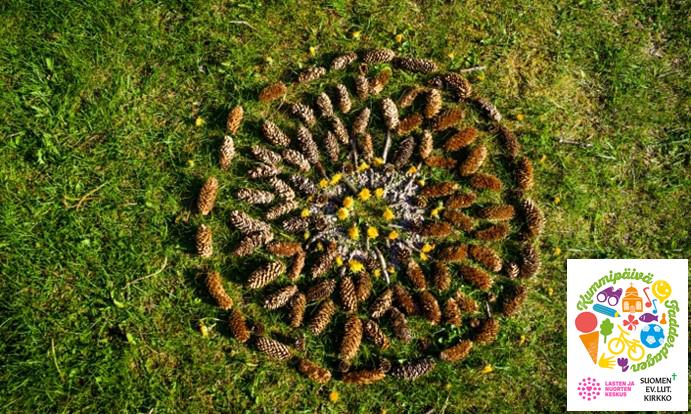 Kävyistä muotoiltu pyöreä mandalakuvio nurmikolla.