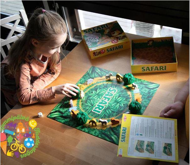 Noin kymmenenvuotias tyttö pelaa lautapeliä keittiön pöydän ääressä.